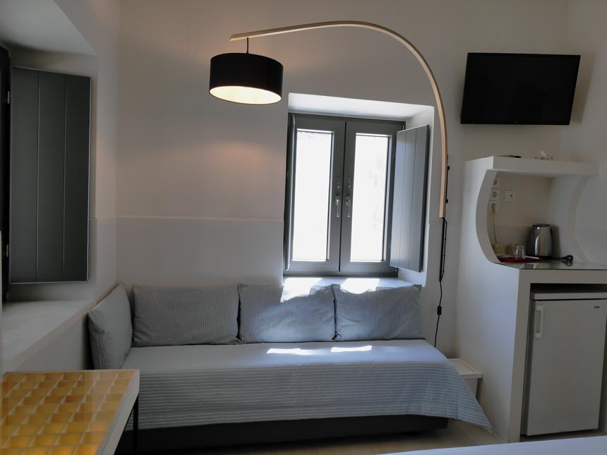 Cycladic minimal style: Partial view of the sofa bed and curvy floor lamp of a triple bedroom at Hotel Emily in Syros.