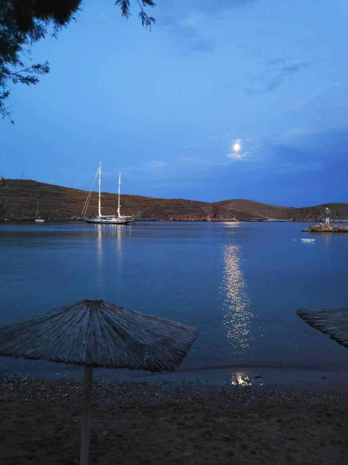 The moon peaking through the clouds casting a glare over the blue waters and the sailing boat with its lights on frame this idyllic view from the beach of Achladi in Syros.
