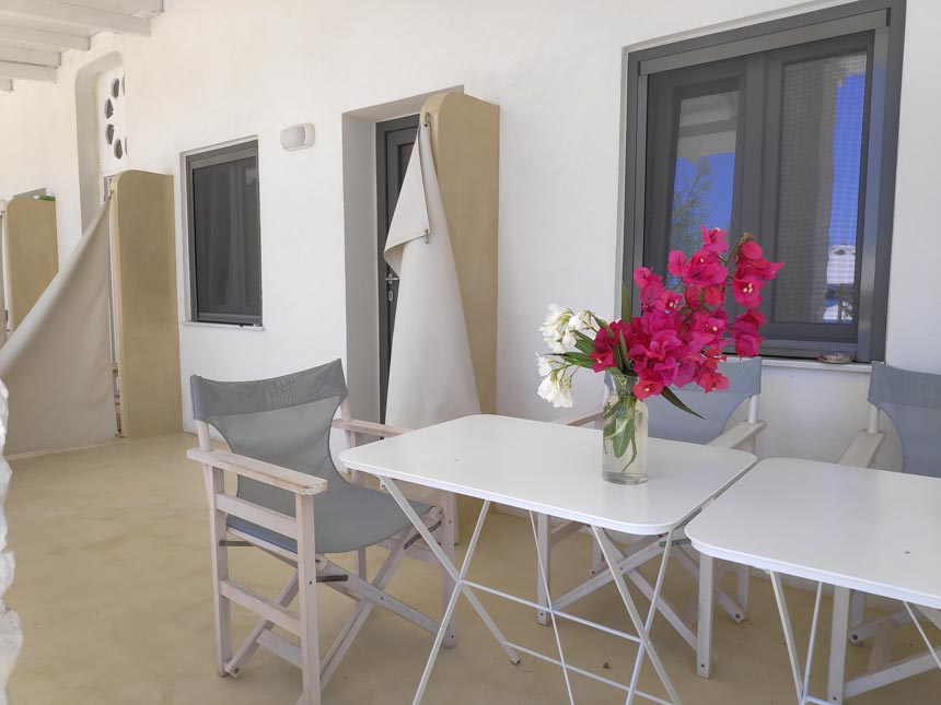 Partial view of the external facade of a room from Hotel Emily in Syros, with microcement flooring and a dining set for the guests to enjoy.