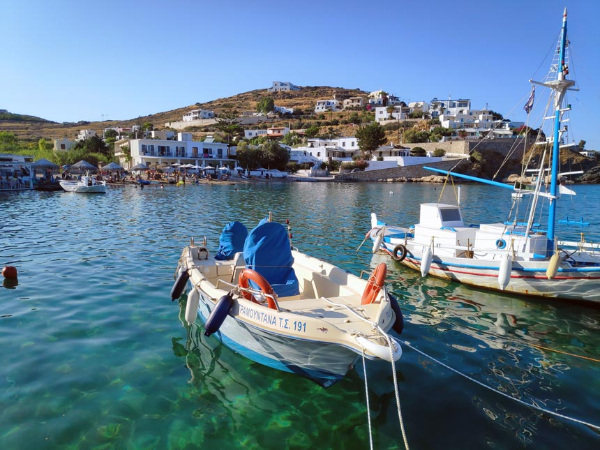 View of Hotel Emily in Syros from afar with the sparkling blue green waters and fishing boats in the foreground.
