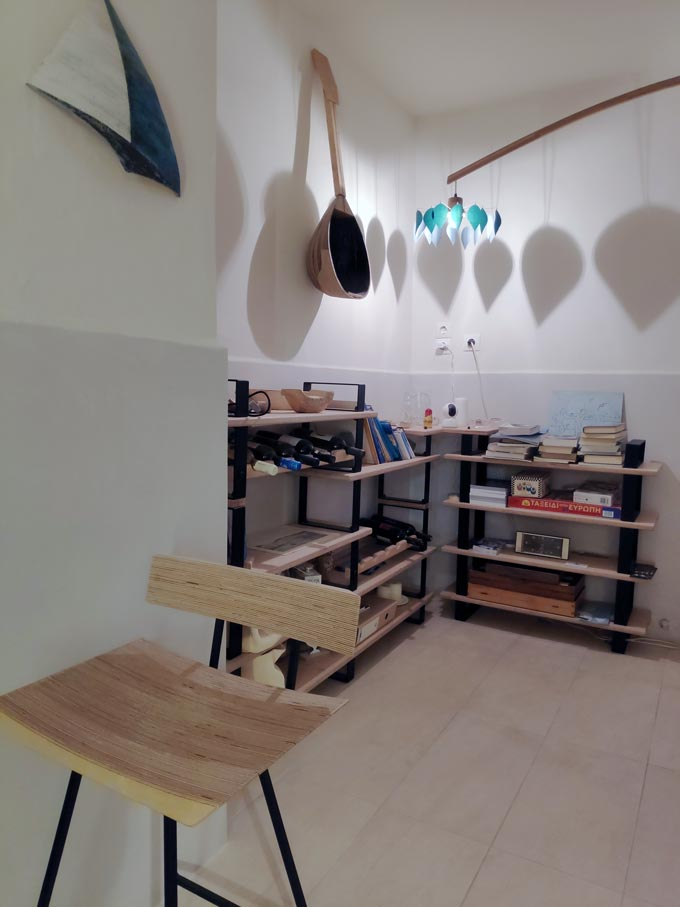 Cycladic minimal style: Racks of shelves with table games, wine bottles and decor at the reception lobby of Hotel Emily.