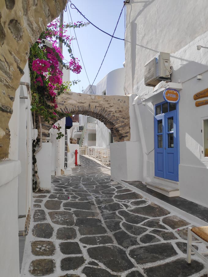 A stone cobbled alley with white washed houses at Naoussa, Paros.