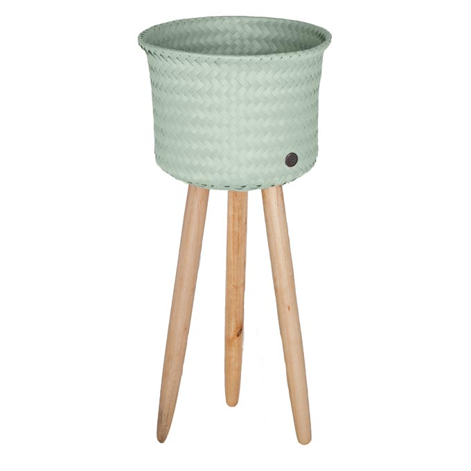 A tall planter with high wooden legs and a pastel green basket. Image by TakaTomo.de.