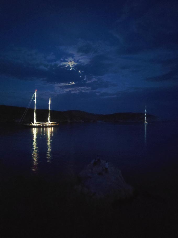 Two sailing boats in a cove while the moon is covered with clouds, barely peaking.