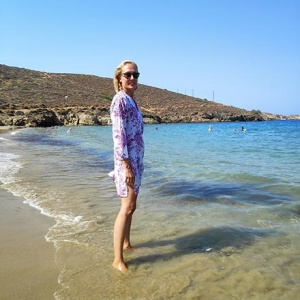 Velvet standing with her feet in the sea at Komito beach in Syros.