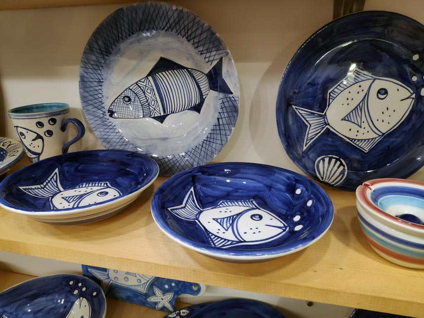 Ceramic platters by Maria Banou with fish painted on them.