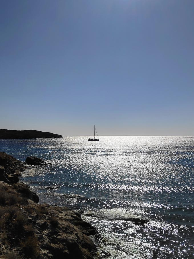 The silhouette of a sailing boat in a sea under midday's summer sun.