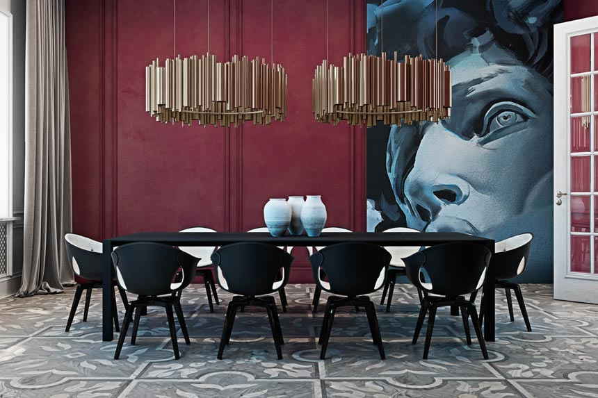 View of a gorgeous dining room featuring a burgundy accent wall with an oversized artwork, gold metallic pendant lights and a black and white dining set.