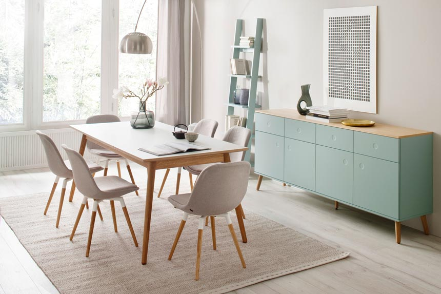 A Scandi sideboard in soft pastel green stands out in this dining space. Image by designbotschaft GmbH.