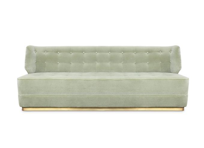 A beautiful stylish sofa in a greyish soft green velvet.