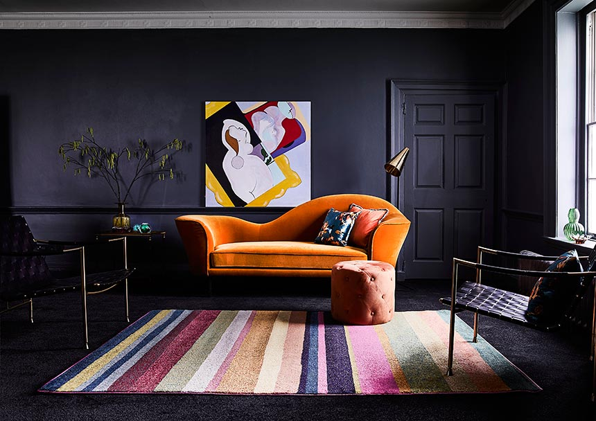 A inky grey room with a statement rusty hue sofa over a multicolored striped area rug. Image by Carpetright.