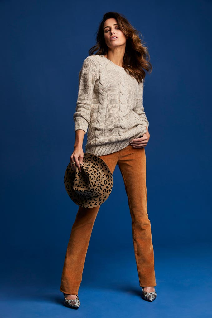 A stylish woman in a cord knot jumper over some rusty hue velvet pants paired with a leopard print hat. Image by Cotton Traders.