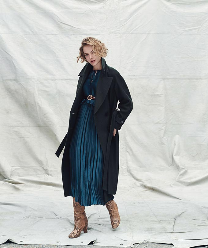 Fall fashion ideas: A dark blue teal top over a pleat skirt paired with beige suede boots and a dark coat. Image by Dorothy Perkins.