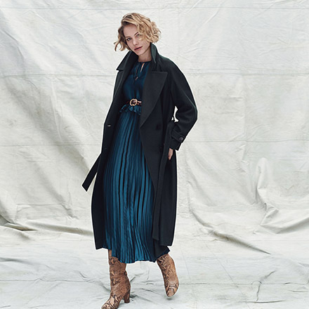 A dark blue teal top over a pleat skirt paired with beige suede boots and a dark coat. Image by Dorothy Perkins.