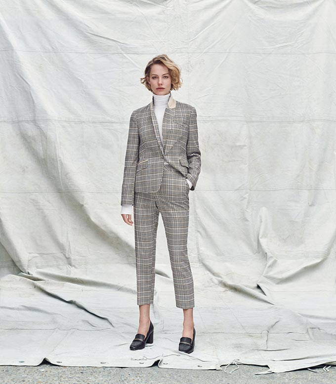 A grey tartan patterned suit paired with a white turtleneck. Image by Dorothy Perkins.