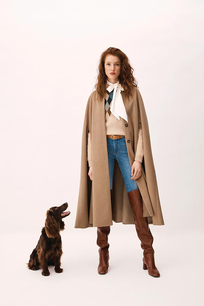 A woman standing next to a dog wearing a classic knit and scarf over some denim pants and tan suede over the knee boots and a camel coat over it.