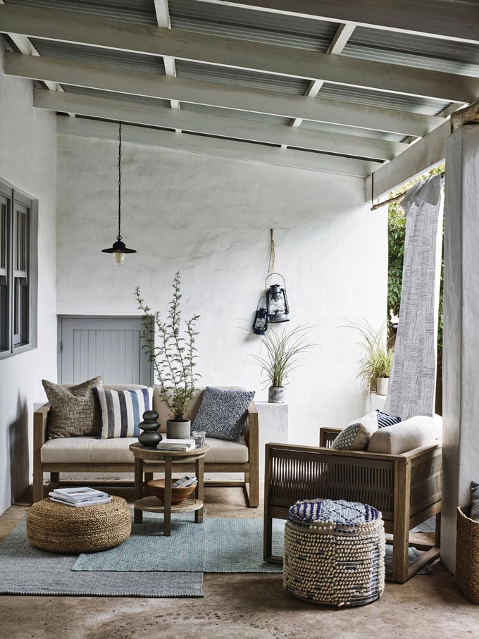 A stylish outdoor space under a rustic pergola, with sofa and armchair and lots of pillows and poufs for sitting comfort. Image via John Lewis.