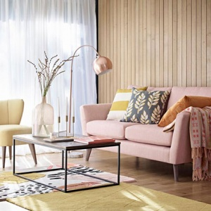 A warm and inviting living room with a soft blush pink sofa, an off white armchair, a coffee table and a wooden accent wall. Image via Marks&Spencer.