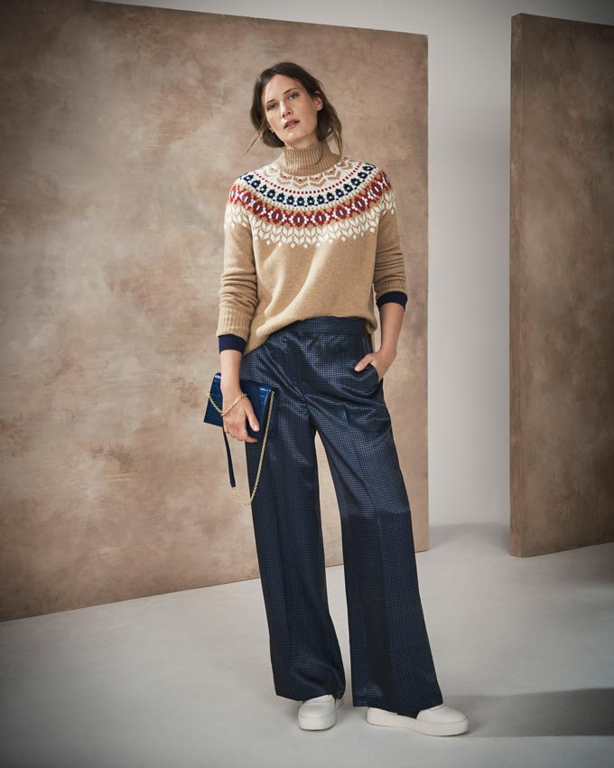 Fall fashion ideas: I like this combo of a beige with a pattern around the neck knit over some loose straight dark blue shiny pants paired with a handbag of the same color and white trainers. Image by Marks&Spencer.