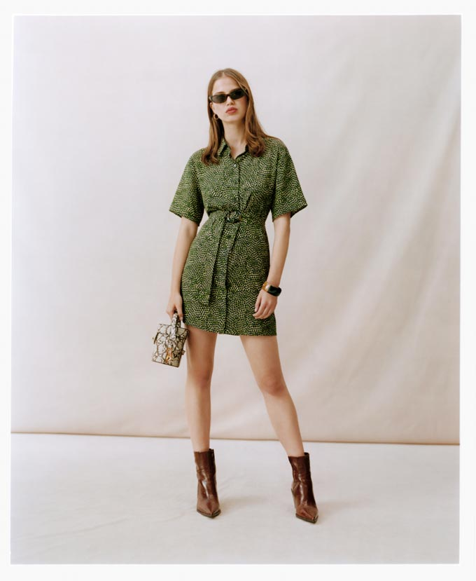 A mini green print dress paired with a small handbag and ankle boots. Image by Topshop.