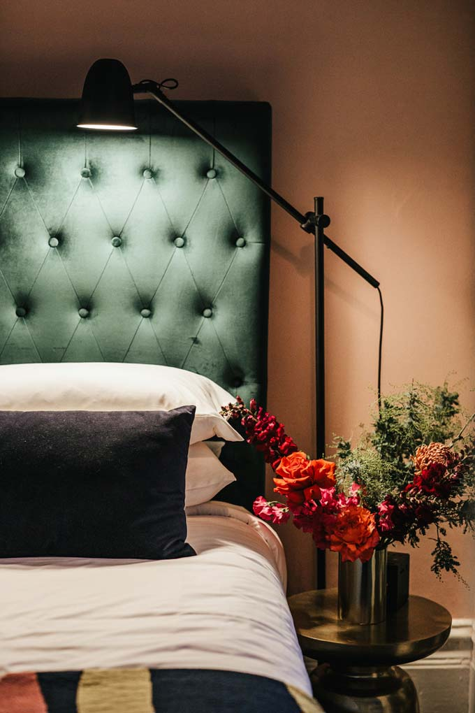 Detail view of a green headboard and bed from one of the rooms of Hotel Harry at Surry Hills, Sydney.