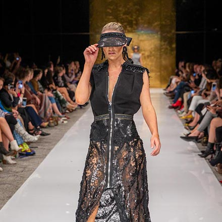 Model in a black lace dress from Maison Garde walking down the catwalk. Image via uncommonstore. Photographer - Richard Smith.