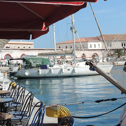 Partial view of the dock at Ermoupolis Syros with sailing boats docked and the Customs Office in the background. Image by Velvet.