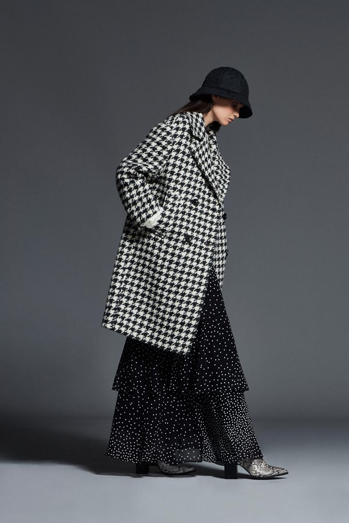 A woman dressed in a coat and a black maxi dress wearing snake print ankle boots. Image via Debenhams.