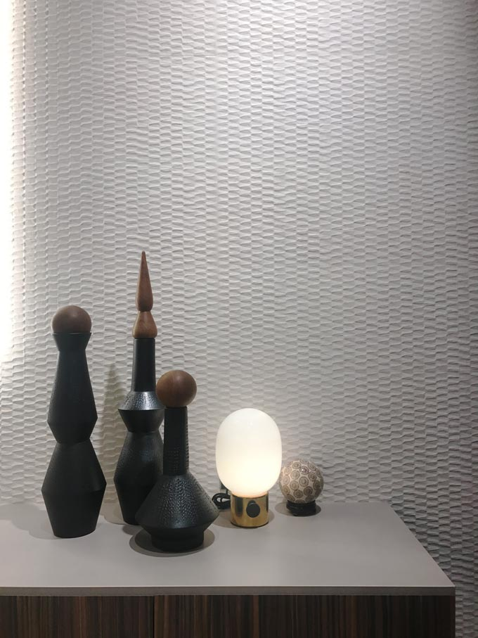 A white 3d effect tile acts like an accent wall behind some black decor. Tile from FAP an Italian company.