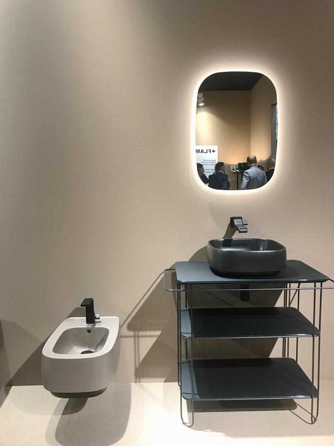A bathroom installation at the fair of Cersaie 2019 of a beige toilet and a black vanity against a beige wall at the stand of Flaminia.