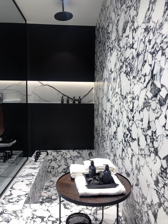 A stunning black and white bathroom with a tub that continues to become an accent wall out of marble tiles.