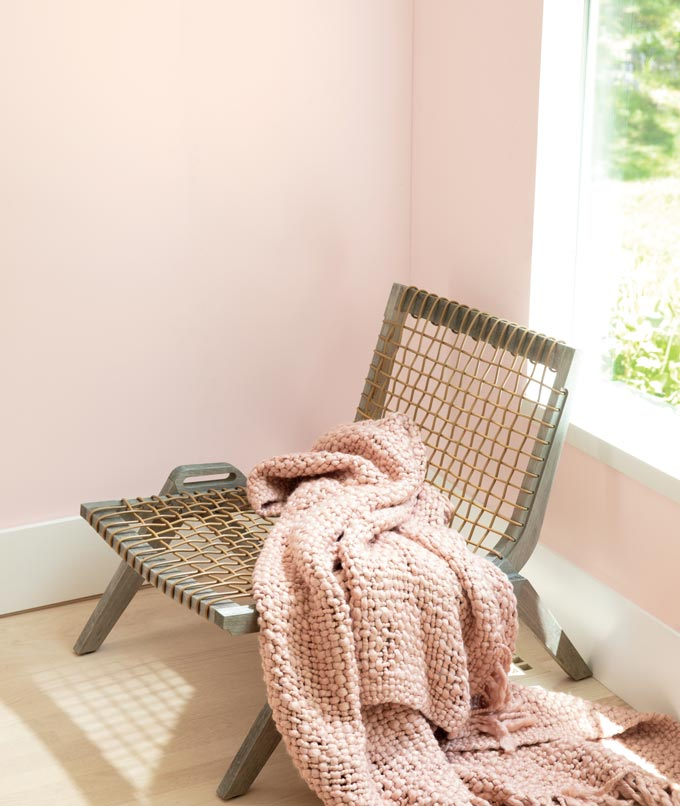 A rattan chair with a pink throw by a corner with a wall painted with BM's first light. Image via Benjamin Moore.