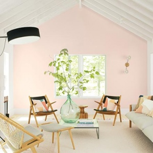 A contemporary and very brights living room with a soft pink wall in the background known as First Light from Benjamin Moore. Image via Benjamin Moore.