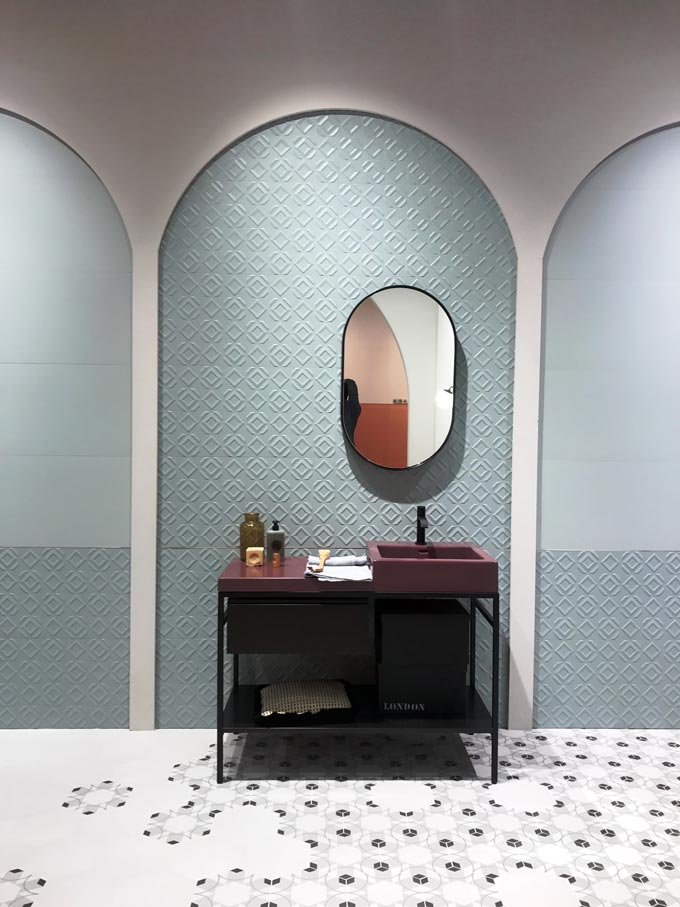 A cyan textured tile on an exhibit booth at Cersaie 2019 with a deep burgundy vanity stand and mirror in front of it. A brilliant setup.