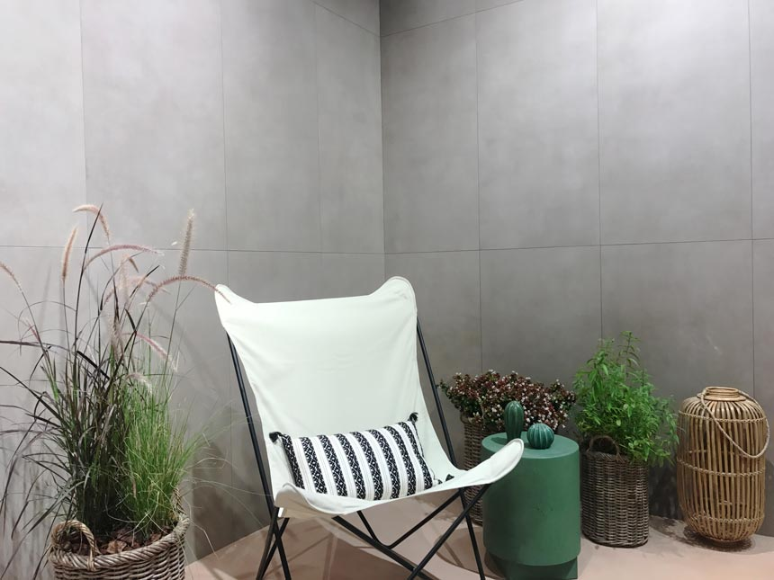A vignette setup as if outdoors with stone looking tiled walls at an installation at Cersaie 2019. Stand of Marca Corona.