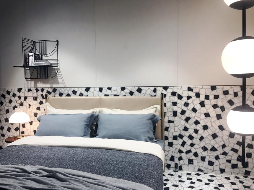 Terrazzo looking tiles extending from the floor up to half way up the wall to make an accent behind a neutral contemporary bed. All that as seen at Ragno's stand at Cersaie 2019.