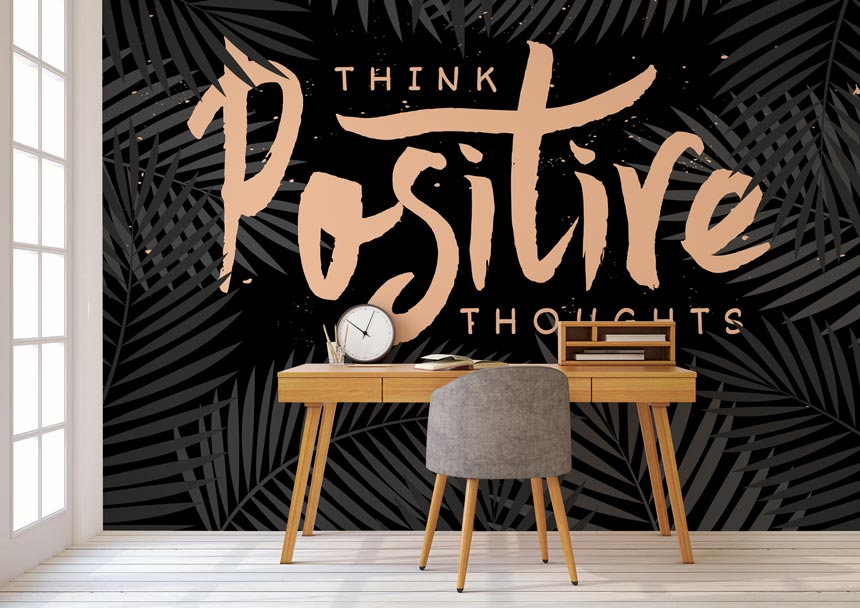 Think positive thoughts wall mural in the background and a study desk in the foreground. Image by Wallsauce.
