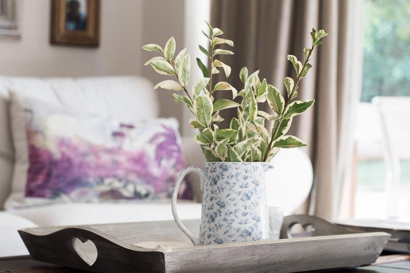 A ceramic jug with greenery on a tray as decor in the foreground and a sofa with pillow in the background.
