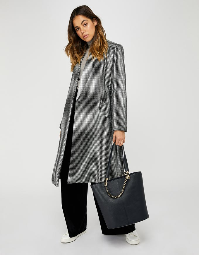 A houndtooth pattern coat over a pair of wide leg black pants, white trainers and a black bag. Image via Accessorize.