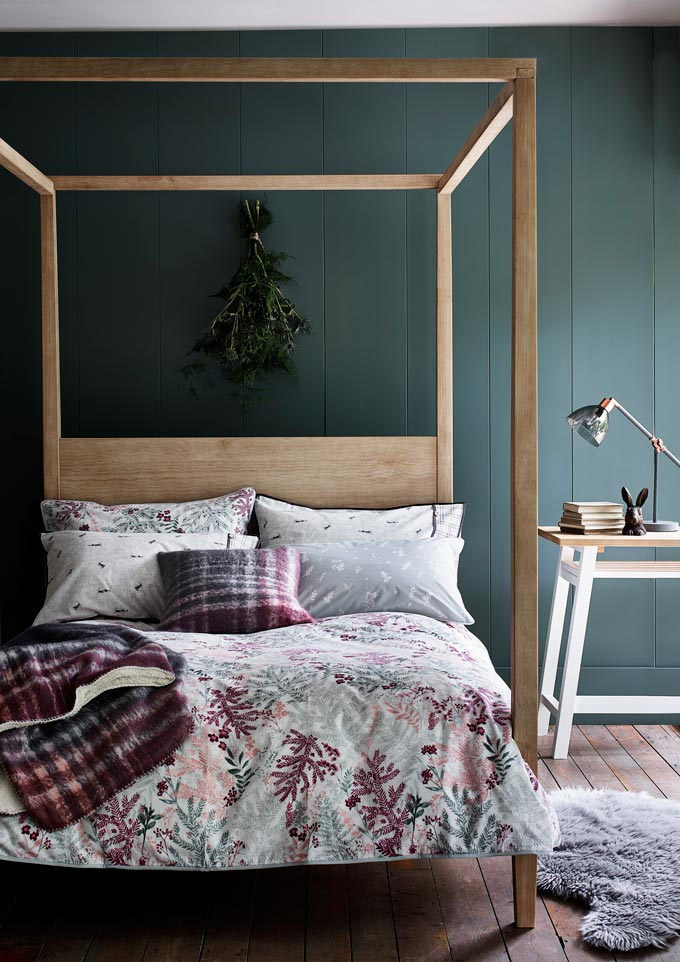 What a cozy and inviting bedroom with a rustic bed and a green accent wall. Image via Argos.