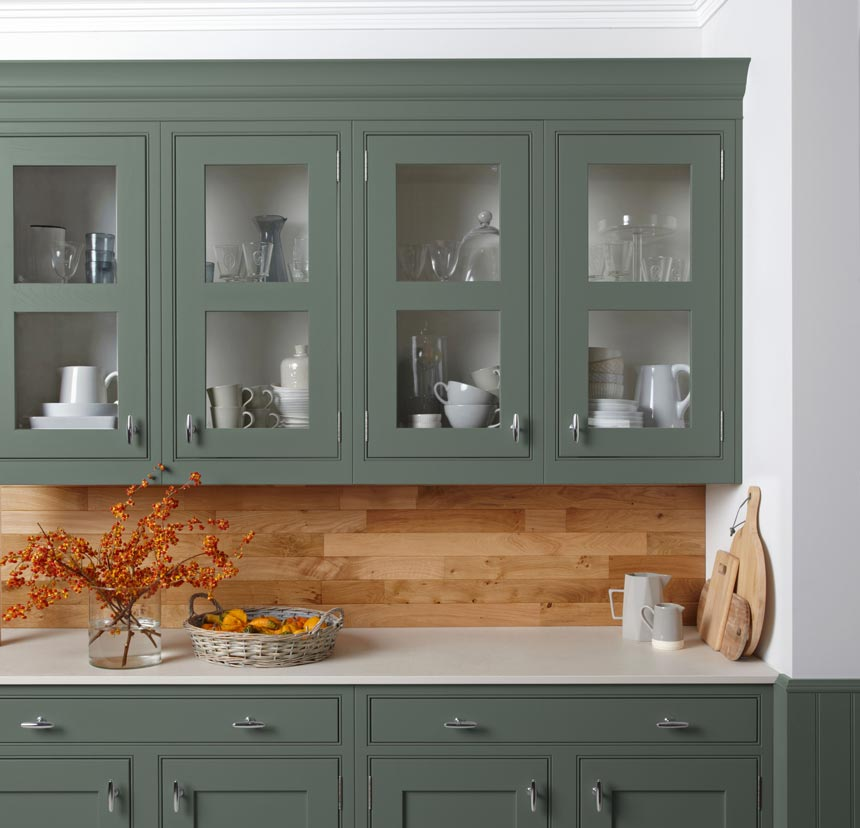 Detail of a beautiful green kitchen cabinetry with a wooden backsplash. Image via Burbidge.