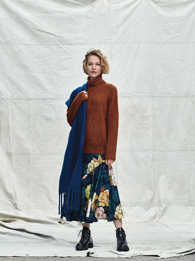 A woman dressed in a rusty hue jumper, a midi flower pattern skirt and black combat boots. Image via Dorothy Perkins.