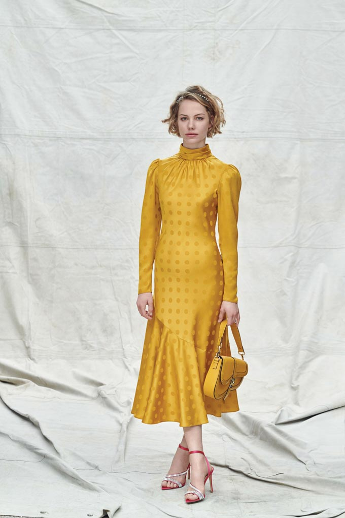 A yellow dress with a yellow saddle bag and high heel sandals. Image via Dorothy Perkins.