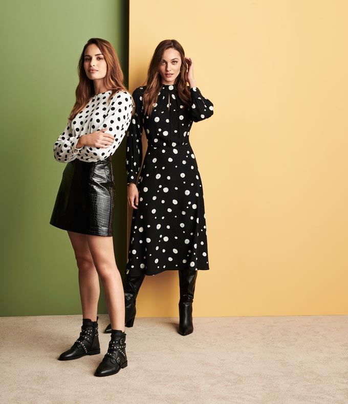 Two women dressed in polka dot outfits. One of them is wearing a black leather mini skirt and black ankle boots with buckles. The other is wearing knee high boots. Image via Dorothy Perkins.