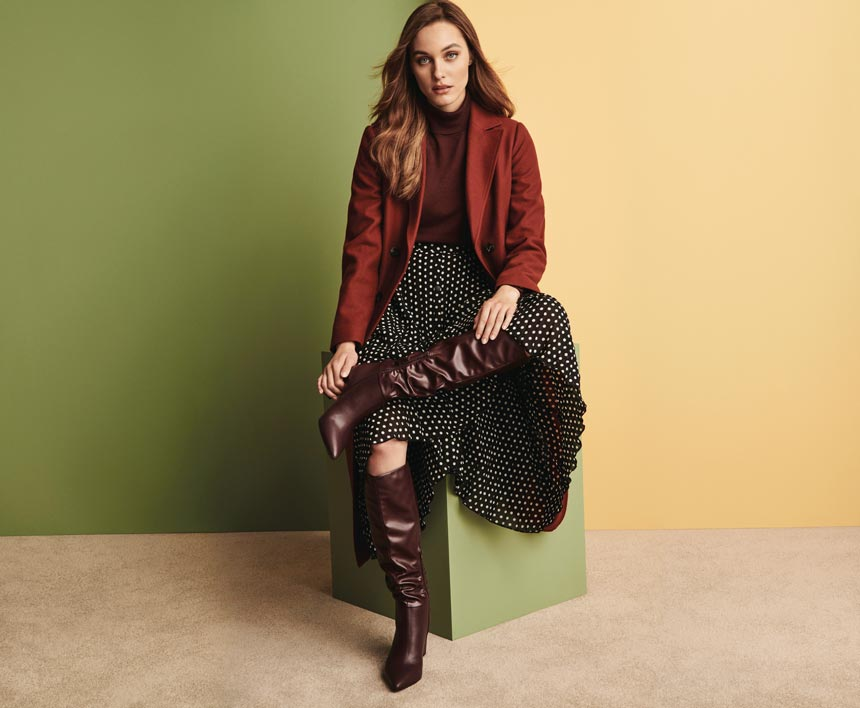 Winter outfits lookbook: A stylish outfit with a burnt orange top, a polka dot pleat skirt, knee high boots and jacket. Image via Dorothy Perkins.