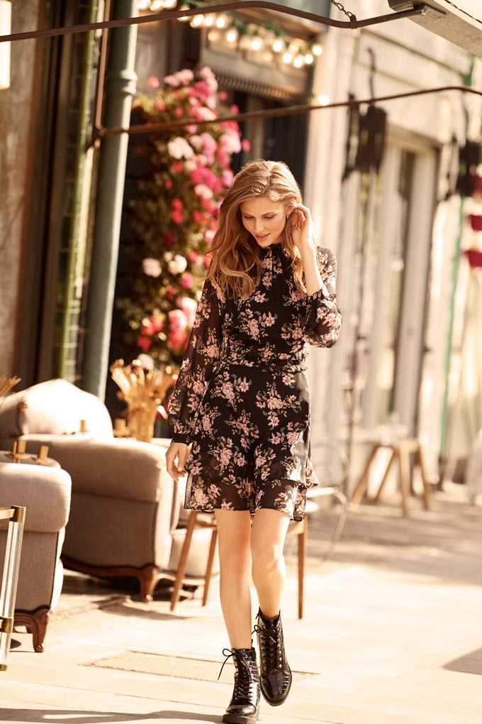 A woman dressed in a black pattern dress and laced up ankle boots walking down the street. Image via Dorothy Perkins.