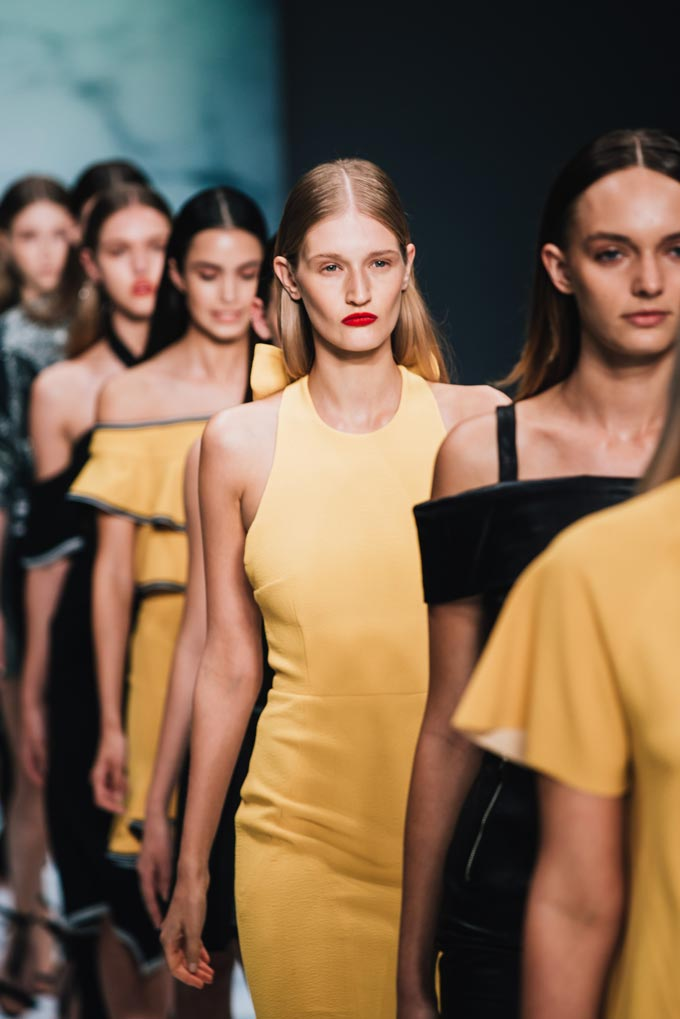 A catwalk will models wearing black or yellow outfits during a fashion show.