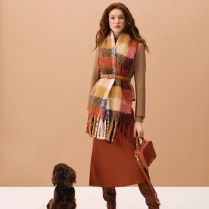 A pasmina worn over a camel coat and a burnt orange skirt and slouchy boots. Note the colors both that cute dog and woman sport so well. Image via Hobbs.
