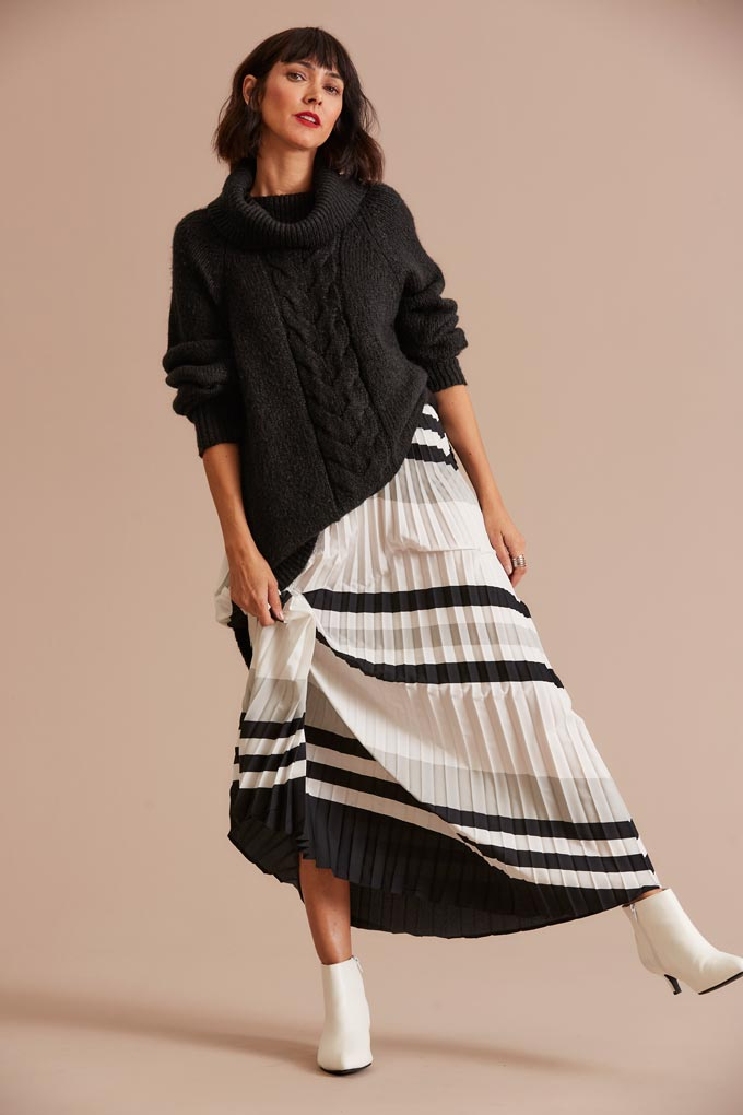Winter outfits lookbook: A striped black and white pleat skirt paired with white booties and a black knit. Image via JDWilliams.