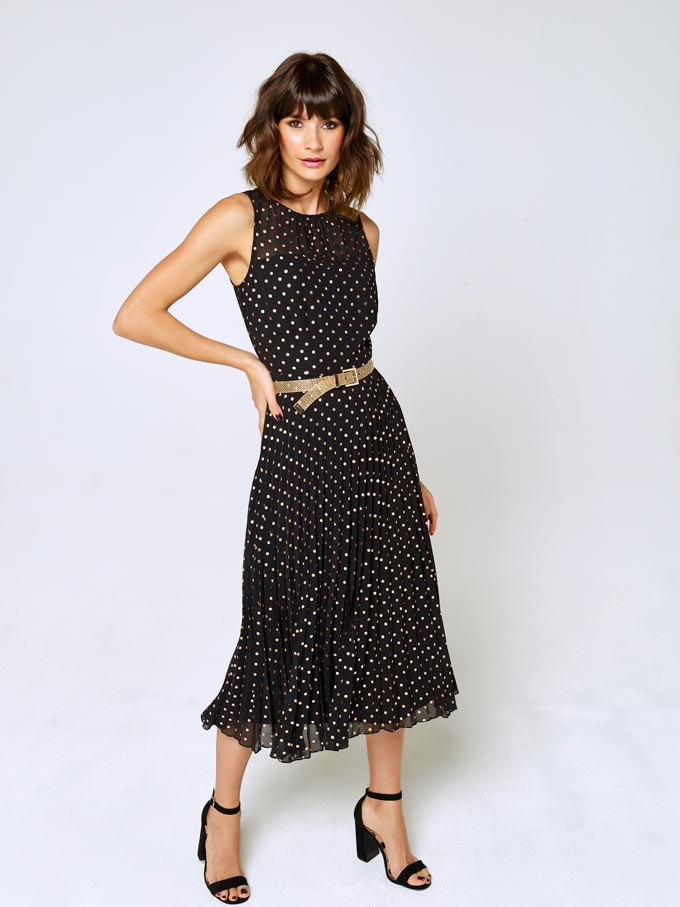A woman in a black polka dot dress paired with black sandals. Image via M&Co.
